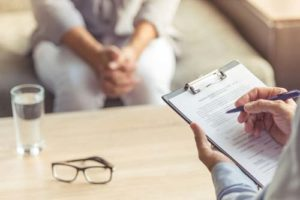 doctor with clipboard and patient addiction counseling glendale az